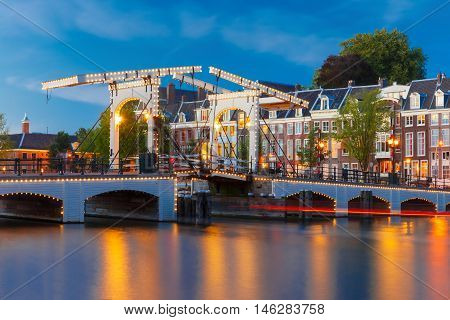 Magere Brug, Skinny bridge, with night lighting over the river Amstel in the city centre of Amsterdam, Holland, Netherlands
