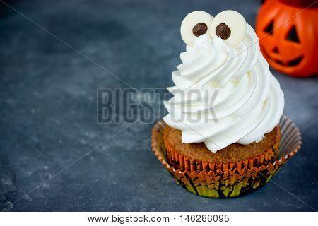 Halloween pumpkin cupcakes with funny meringue ghost idea for Halloween party dessert selective focus