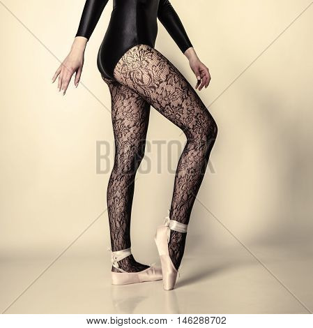 beautiful woman ballet dancer part of body legs in shoes and black lace tights studio shot on gray background