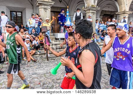 Antigua Guatemala - September 14 2015: Locals run in streets with lit torches while blowing whistles & horns during Guatemalan Independence Day celebrations