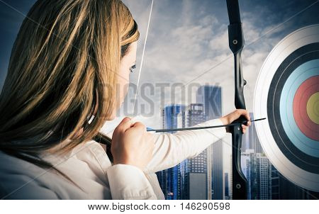 Businesswoman with bow and arrow pointing the center of the target