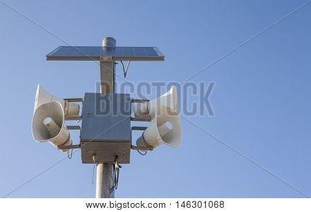 Solar-powered megaphones pole against blue sky background