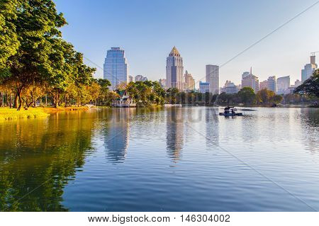 Business district cityscape from a park with Sunset Time from Lumpini Park Bangkok Thailand