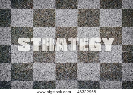 Word Strategy written on textured chessboard as background