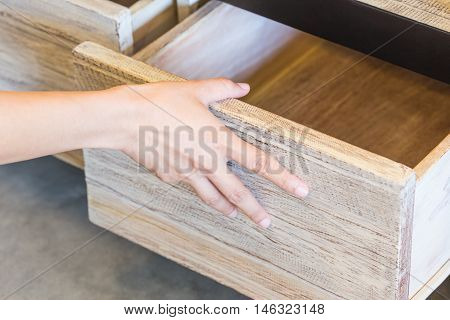 Use right hand pull open drawer wooden in cabinet.