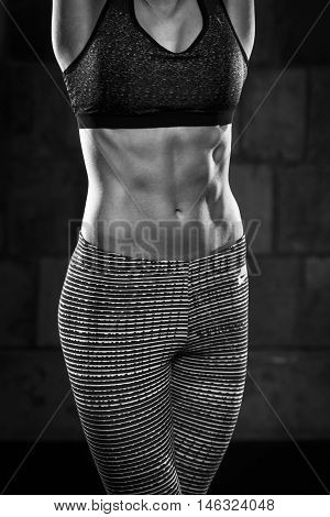 Fitness girl leans against wall in gym with muscles and abs showing after exercise.