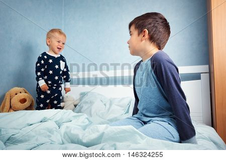 Brothers sitting in the bed in pyjamas