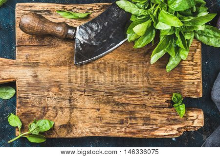 Fresh green basil and vintage herb chopper on rustic wooden bord, top view, copy space, horizontal composition