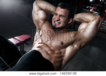 Handsome bodybuilder doing exercises for abdominal muscles on an incline bench at the gym. The concept of sports and healthy lifestyle.