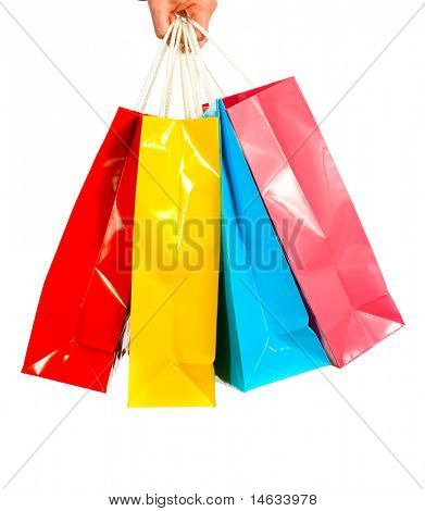 A ladies hand gripping several brightly colored shopping bags on a white background