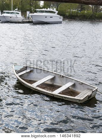 Small sinking boat with water inside of a beautiful modern boats.