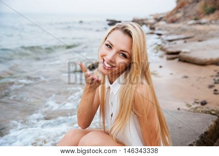 Smiling young blonde woman blowing air kiss at rocky beach on a sunny day