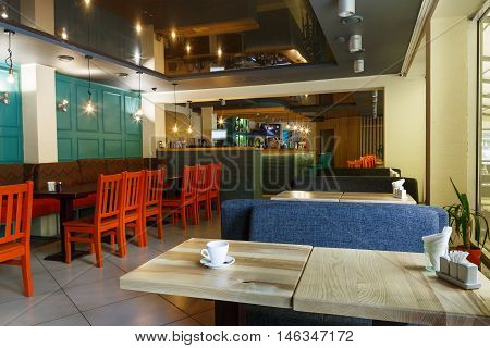 Modern restaurant or cafe interior. Public place interior design, bright red wooden chairs and blue sofas, large windows and bar. Morning light, nobody indoors.