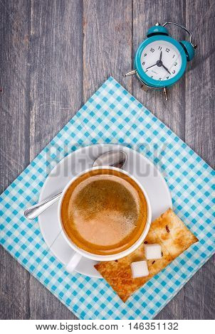 Cup of hot morning coffee on saucer with sugar spoon blue napkin and alarm clock on wooden board in rustic style