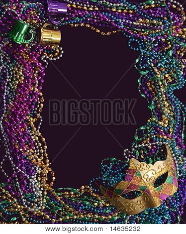 A group of Mardi Gras beads and mask making a frame with copy space on a purple background