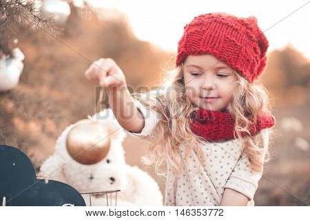 Smiling kid girl 4-5 year old holding christmas ball wearing knitted red hat and scarf outdoors. Winter portrait. Christmas holidays.