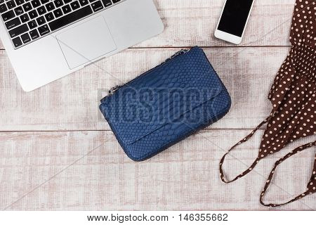 Ladies Fashion Accessories. Luxury handmade snakeskin (python) handbag, dress, laptop, smartphone. Top view, flat lay, light wooden  background. Free/empty space for text.