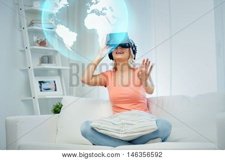 technology, augmented reality, entertainment and people concept - happy young woman in virtual headset or 3d glasses and headphones playing game at home looking at projection of earth globe