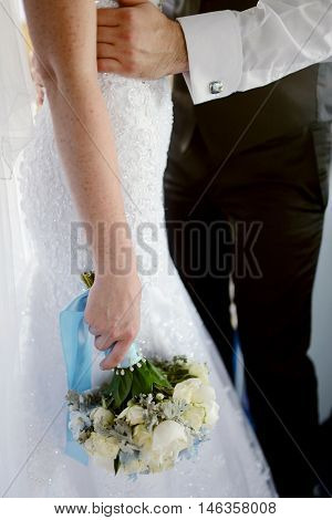 Wedding couple with bouquet. Female and male portrait. Beautiful model girl in white dress. Man in suit. Beauty bride with groom. Woman in bridal gown. Cute lady and guy indoors