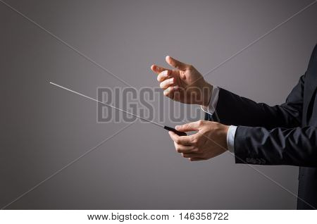 Closeup of hand of conductor ready to direct. Hand of music conductor on gray background. Music director guiding orchestra to play the band.