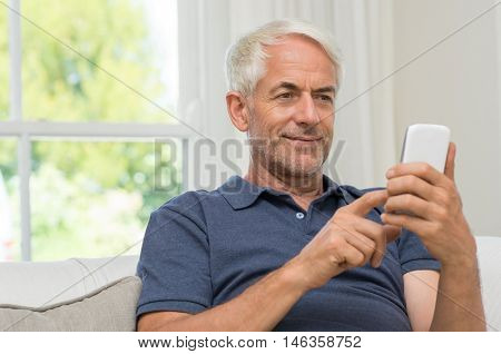 Senior man sitting in couch reading text message on smartphone. Mature smiling man using smart phone at home. Portrait of happy retired man texting a message phone.