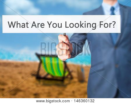 What Are You Looking For ? - Businessman Hand Holding Sign