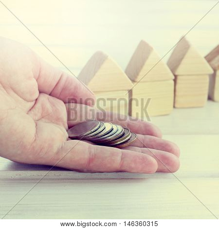 lots of coins lying on the palm on background blurred wooden houses / receiving the transfer of means of payment on the property