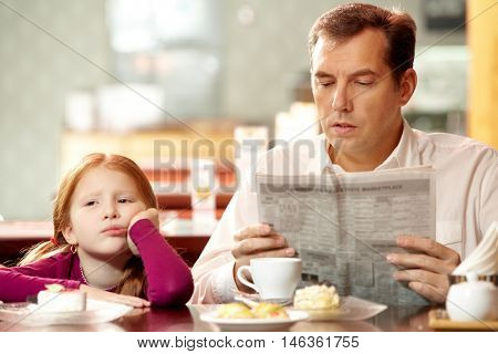 Bored girl sitting in cafe with her father who is reading paper