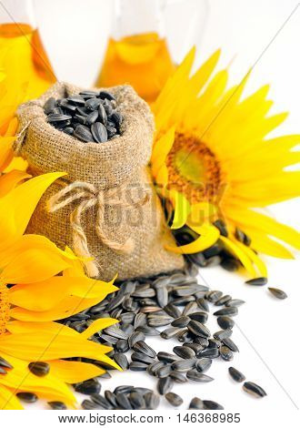 Small Bag With Sunflower Seeds On A Background Of Flowers And A Bottle Of Sunflower Oil