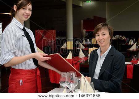friendly waitress presented the guest the wine list