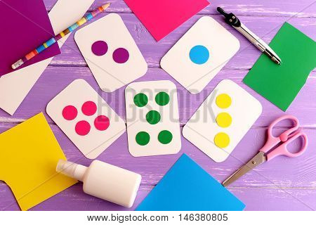 Flash cards for toddler, preschooler. How to teach kid to read colors. How to teach a kid to count. Flashcards, scissors, pencil, cardboard on wooden background. Top view. Early childhood development