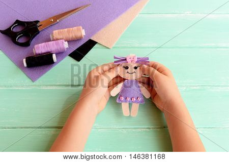 Child holds a small doll in his hands. Child shows a felt doll. Scissors, thread and felt set on a wooden table. Easy fabric art and craft idea for kids