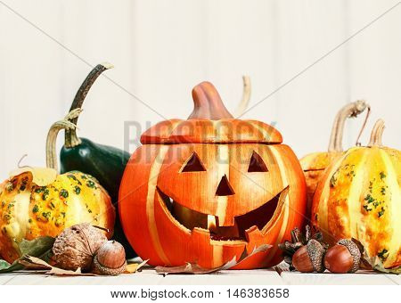 Halloween holiday still life happy scary pumpkin jack-o-lantern with dry leaf and acorns on wooden board close-up
