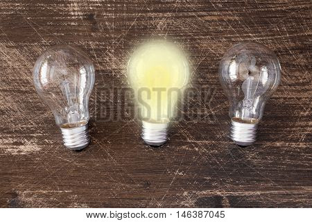 Lightbulb glowing among the others. Uniqueness concept.