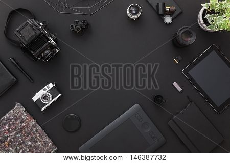 Work space on black table of a creative designer or photographer with laptop tablet cameras other objects of inspiration and copy space. Stylish home studio concept of technology trends.