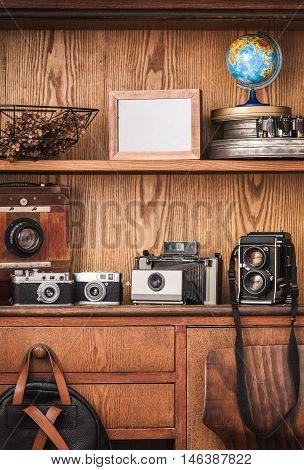 Photographer locker with old fashioned cameras.  Black and white photography.