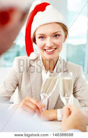 Portrait of happy businesswoman in Christmas hat clinking glasses with her colleague