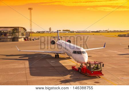 Airplane at sunset in the terminal gate ready for takeoff - Waiting for the flight.Travel around the world