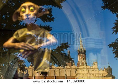 KRAKOW, POLAND - FEB 8, 2016: The reflection in the window of Polonia Wax Museum at Main Market Square. The Wax Museum was opened in 2016, inspired by the organization in Krakow World Youth Day.