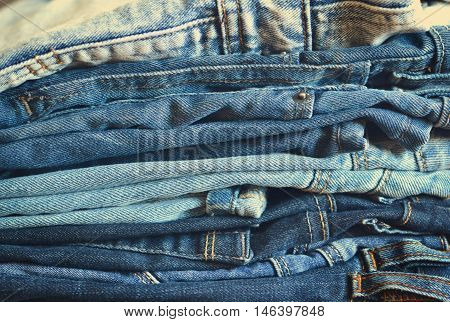 Fashionable and stylish clothes - a lot of different blue jeans closeup on wooden background