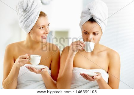Two young girls drinking tea at bathhouse