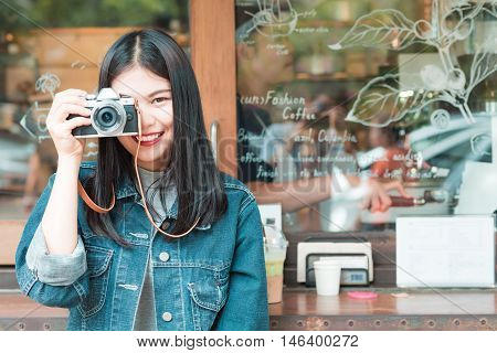 Portrait Of Asian Beautiful Young Hipster Woman With Mirrorless Camera In Cafe