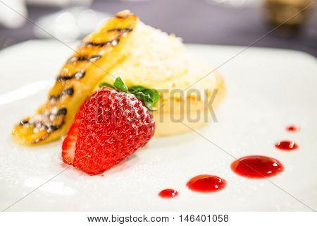 Custard cream tart dessert with fresh strawberries in a restaurant setting