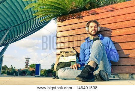 Young man listening music and using mobile phone - Handsome traveler guy with headphones sitting outside modern building looking smartphone and relaxing - Urban concept of travel and communication