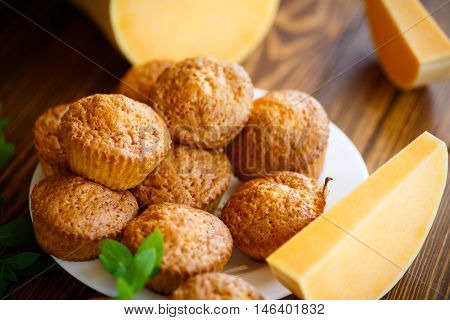 Sweet pumpkin muffins on a wooden table