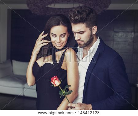 Sexy young romantic man gives rose to stylish woman in luxury hotel room