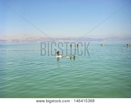 DEAD SEA ISRAEL - MAR 31 2008: People floating on water in the Dead sea Israel.The Dead Sea is second saltiest body of water  with a salt content of 33% that creates a natural buoyancy.