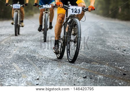 group of riders cyclists ride gravel road. competitions on mountain bike. athlete leader of race