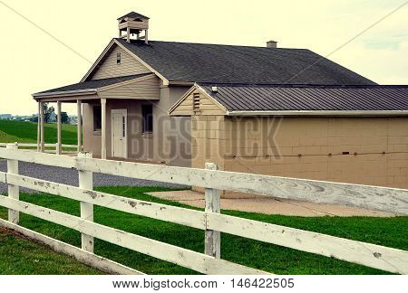 Lancaster County Pennsylvania - June 5 2015: A one-room Amish schoolhouse and buggy shed set amidst rolling farmlands on a country road