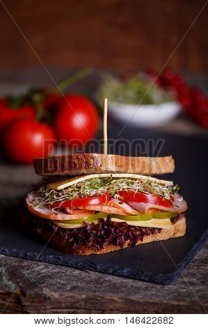 Sandwich with cereals bread with lettuce slices of fresh tomatoes and sweet pepper ham prosciutto salami cheese and onion sprouts on dark marble background. Close-up